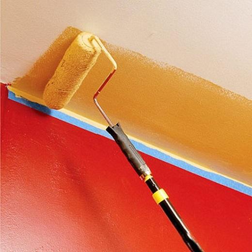 На фотографии показан процесс нанесения краски на потолок