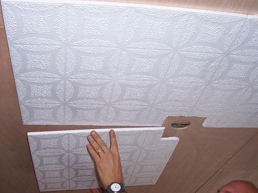 На фото показан процесс поклейки плитки на потолок