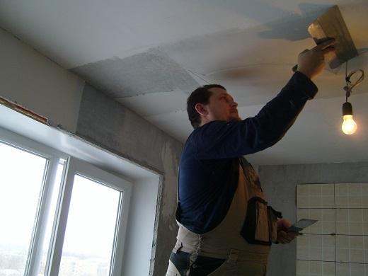 На фотографии показан процесс шпатлевки потолка