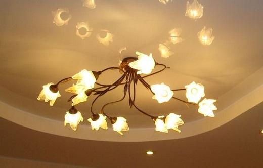 Многорожковая люстра на глянцевом потолке зала