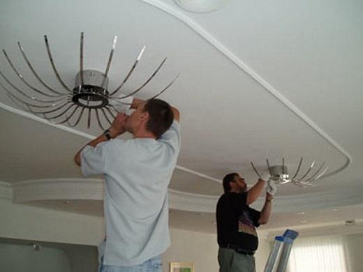 На фото показан процесс монтажа люстры на натяжной потолок