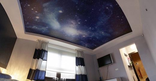 Глянцевый потолок в спальне выполнен в виде звездного неба