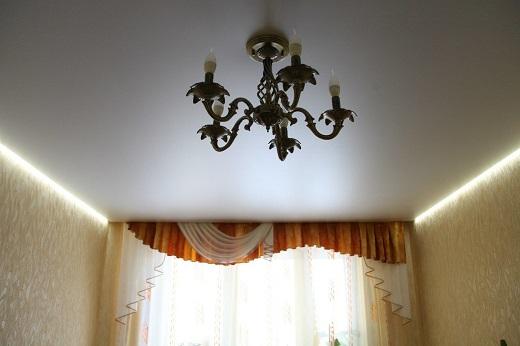 На фото пример натяжного парящего потолка в зале с использование классической подсветки дневного света