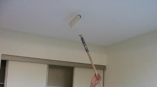 На фото показан процесс нанесения водоэмульсионной краски на потолок