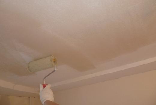 На фото показан процесс нанесения грунтовки на потолок