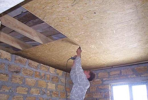 На фото показан процесс подшивки потолка OSB плитами