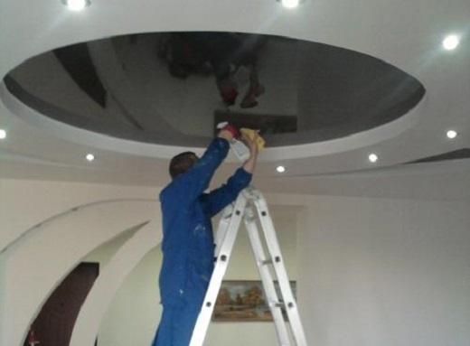 На фото показан процесс чистки комбинированного натяжного потолка